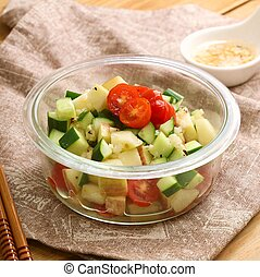 Salad of cube cucumber and tomato in plastic bowl