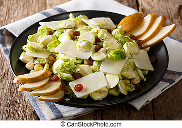 salad of fresh Brussels sprouts with nuts, cheese and fruits close-up. horizontal