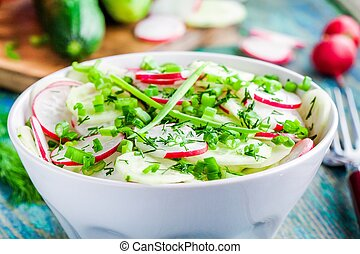 salad of fresh organic radish and cucumber in white bowl closeup