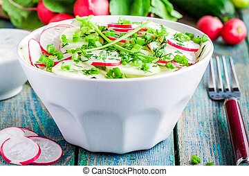 salad of fresh organic radish and cucumber in white bowl for lunch