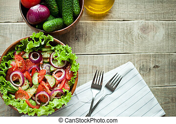 Salad of fresh tomatoes, cucumbers, red onions and lettuce, dressed with olive oil and ground pepper in a wooden bowl. Top view