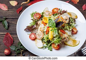 Salad of fresh vegetables with arugula, basil, shrimp and pear