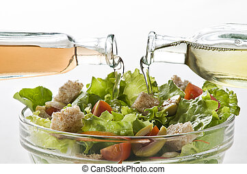 Salad - Olive oil and vinegar pouring in to green salad