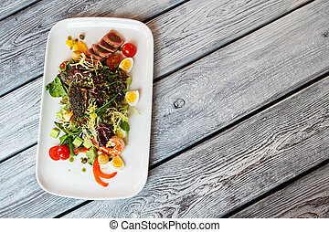 Salad on long white plate.