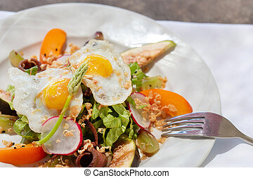 Salad plate with smoked duck breast and fried eggs on the ...
