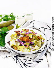 Salad potato with bacon and cucumber in plate on light board