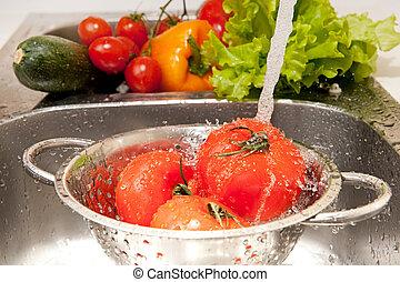 Salad preparing - Three fresh tomatoes in colander splashing...