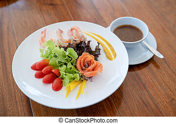 Salad raw salmon arranged to rose shape and boiled shrimp beside in the white dish on wood table.