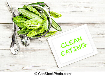 Green salad vegetables with tablet pc on kitchen table. Clean Eating website concept