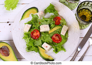 Salad with avocado , cheese and white wine in a transparent glass on wooden table