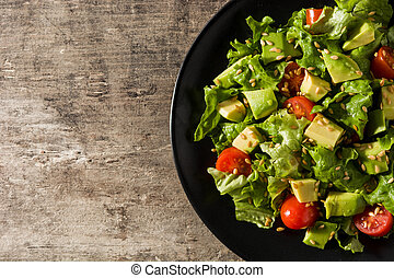 Salad with avocado, lettuce, tomato, seeds on wooden table. Top view. Copy space