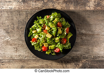 Salad with avocado, lettuce, tomato, seeds on wooden table. Top view