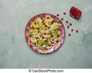 Salad with avocado, pomegranate and pumpkin seeds.