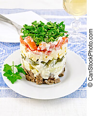 Salad with beef and tomato on blue tablecloth