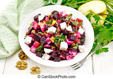 Salad with beetroot and walnuts in plate on board