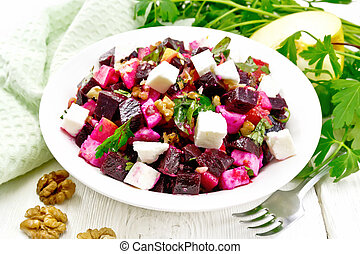 Salad with beetroot and walnuts in plate on light board