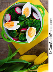 Salad with broccoli, eggs and radishes in a small bowl on wooden background and tulip bouquet.