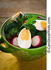 Salad with broccoli, eggs and radishes in a small bowl on wooden background.