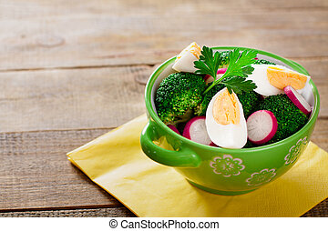 Salad with broccoli, eggs and radishes in a small bowl on wooden background with copy space.