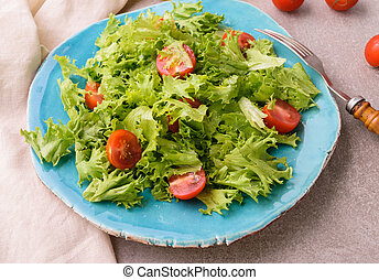 Salad with cherry tomatoes on blue plate