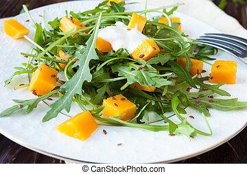 salad with chunks of pumpkin and fresh arugula