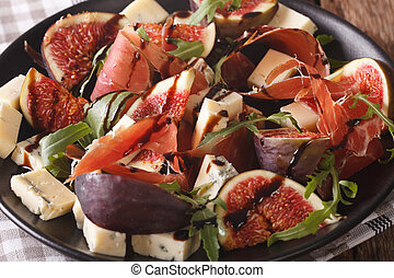 Salad with figs, prosciutto, cheese and arugula macro on a plate. horizontal