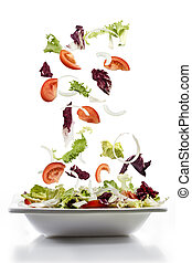 salad with fresh vegetables falling on plate