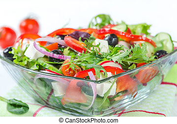 Salad with fresh vegetables in a glass bowl