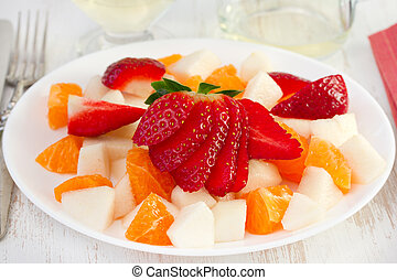 salad with fruits on the white plate with wine