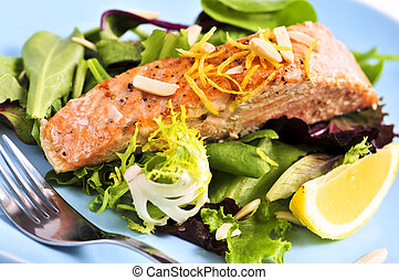 Green salad with grilled salmon fillet and lemon