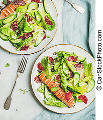 Salad with grilled salmon, orange, olives, fresh cucumber and quinoa
