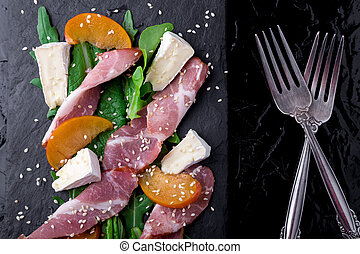 Salad with ham jamon serrano, camembert, melon, arugula on black stone slate plate on black background. Top view