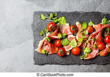 Salad with ham jamon serrano, cherry tomatoes, arugula, slate board