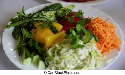 Salad with herbs in a plate on the table.