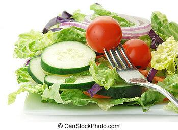 Fresh garden salad with lettuce onion tomato cucumber on white background.