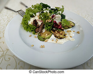 salad with meat. On a white plate.