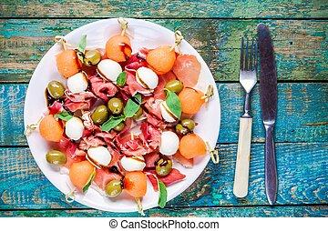 salad with mozzarella, prosciutto, melon and olives