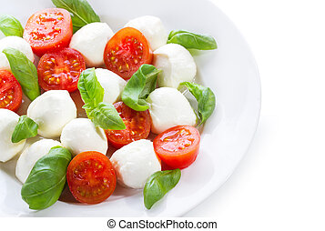 salad with mozzarella, tomatoes and basil on white...