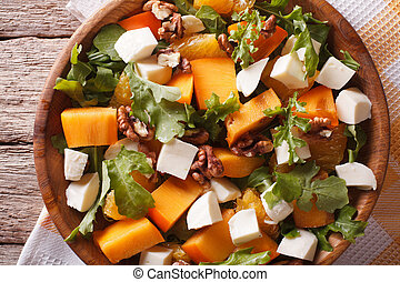 salad with persimmon, arugula and cheese closeup. horizontal top view