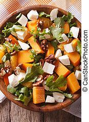 salad with persimmon, arugula and cheese closeup. vertical top view