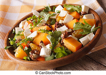 salad with persimmon, arugula, oranges and cheese close-up