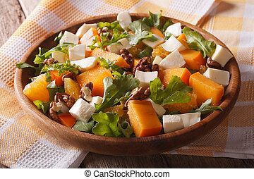 salad with persimmon, arugula, oranges and cheese. Horizontal, rustic