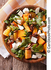 salad with persimmon, nuts, arugula and cheese closeup. vertical top view