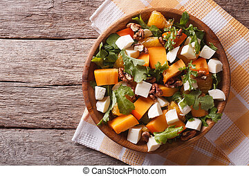 salad with persimmon, nuts, arugula and cheese. horizontal top view