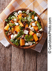 salad with persimmon, nuts, arugula and cheese. vertical top view
