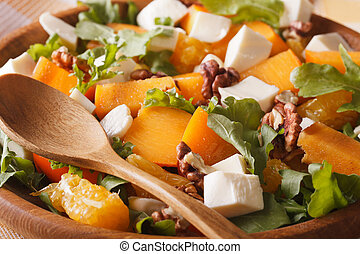 salad with persimmons, walnuts, arugula, cheese and oranges macro.