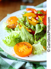 salad with red and yellow peppers and lettuce and tomatoes