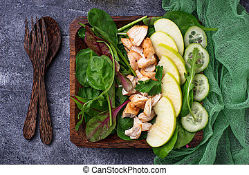 Salad with spinach, chicken, cucumber and apple. Top view