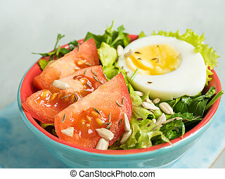 Salad with tomatoes and eggs in a light ceramic plate