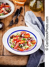 salad with tomatoes, cucumbers, olives, onions, feta and couscous